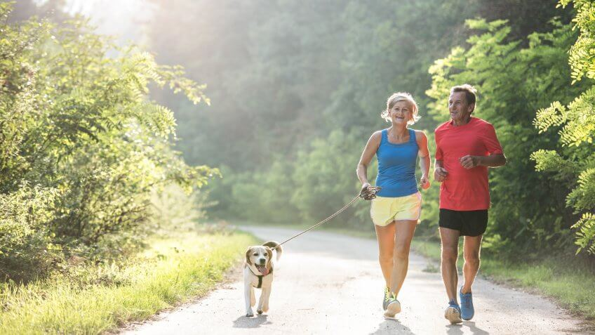 Active senior couple with dog running outside in green sunny nature.