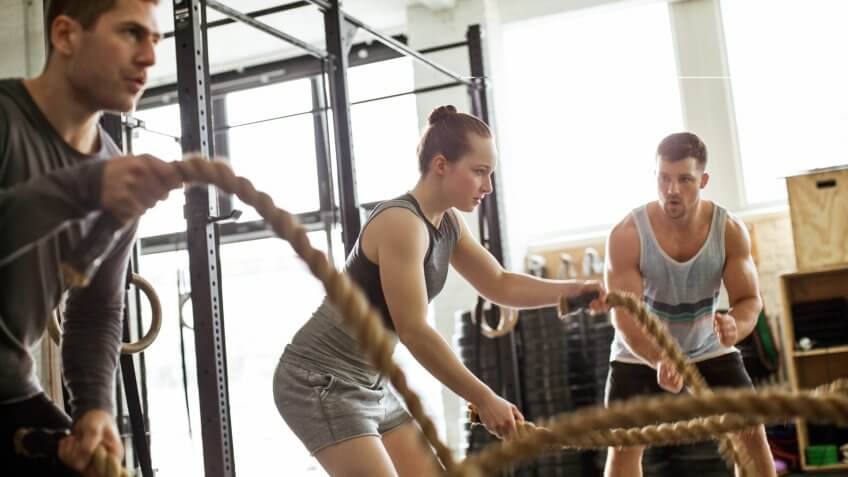 Fitness gym with man and woman working out with battle ropes at the gym.