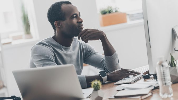 Handsome young African man keeping hand to his face while sitting at his working place in home office.