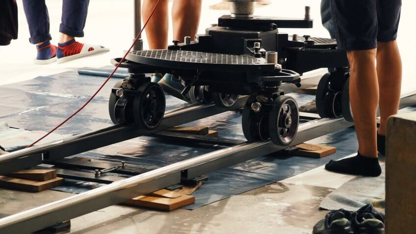 Behind the scenes of production crew team setting dolly track for camera equipment and 4K HD video shooting in a big studio.