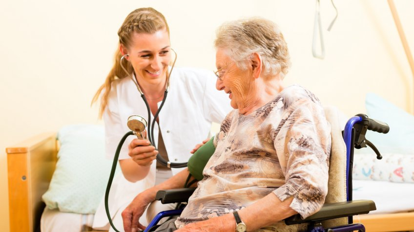 Young nurse and female senior in nursing home, the blood pressure is going to be measured.