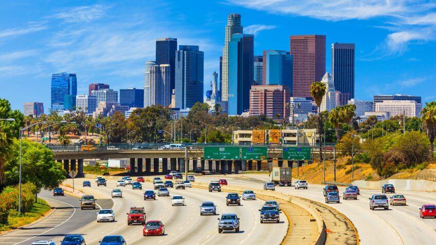 Heavy traffic on freeway leading back to skyscrapers of Los Angele skyline.