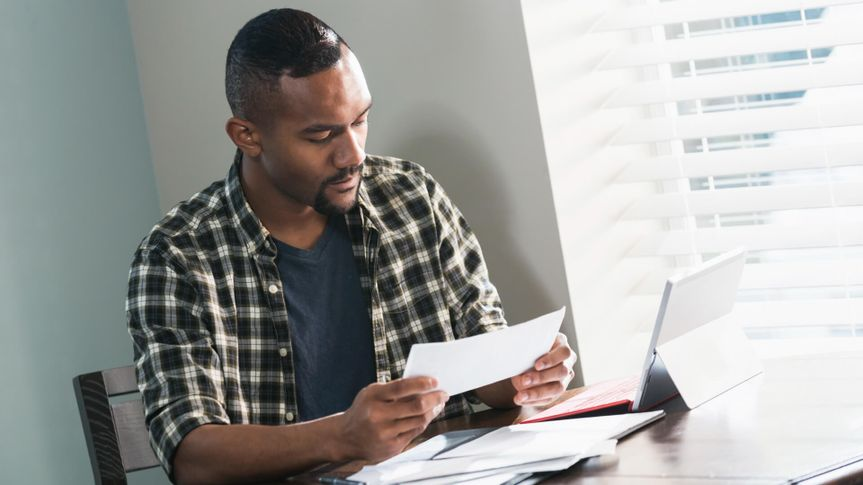 A young African-American man sitting at a table at home, paying bills.
