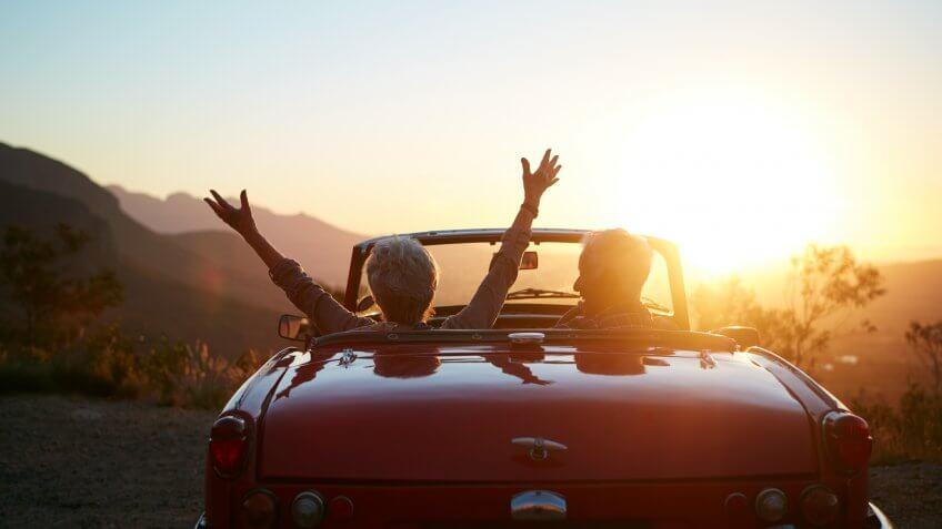 Shot of a joyful senior couple enjoying the sunset during a roadtrip.