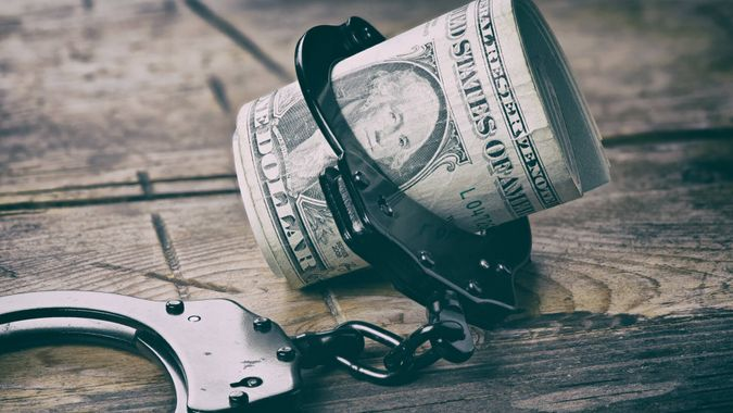 Handcuffs and money on wooden table.
