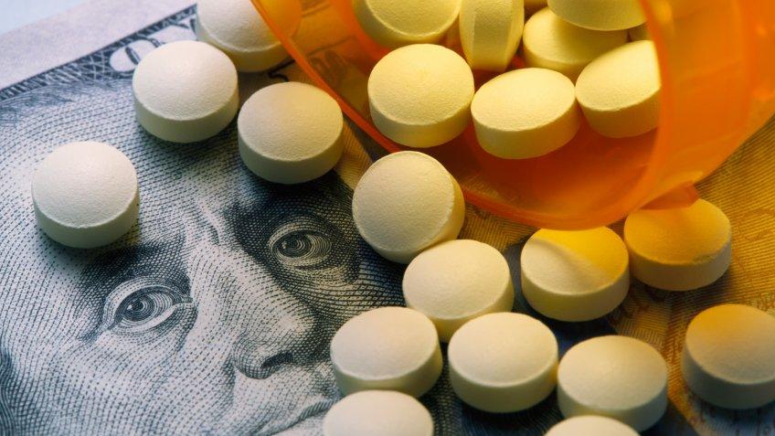 Pills spill out onto a one hundred dollar bill from an open prescription medication bottle.