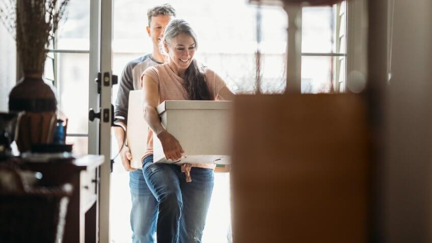 A couple in their 50's moves in to their new home, unpacking boxes and enjoying the time together.