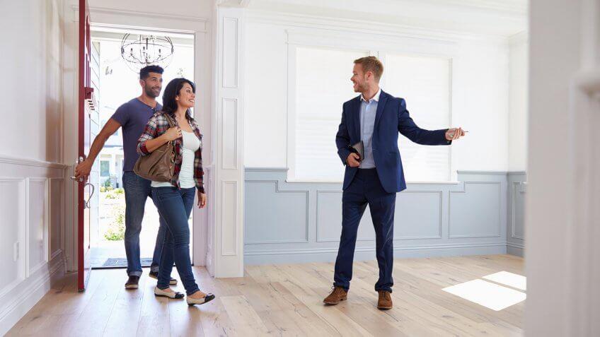 Realtor Showing Hispanic Couple Around New Home.