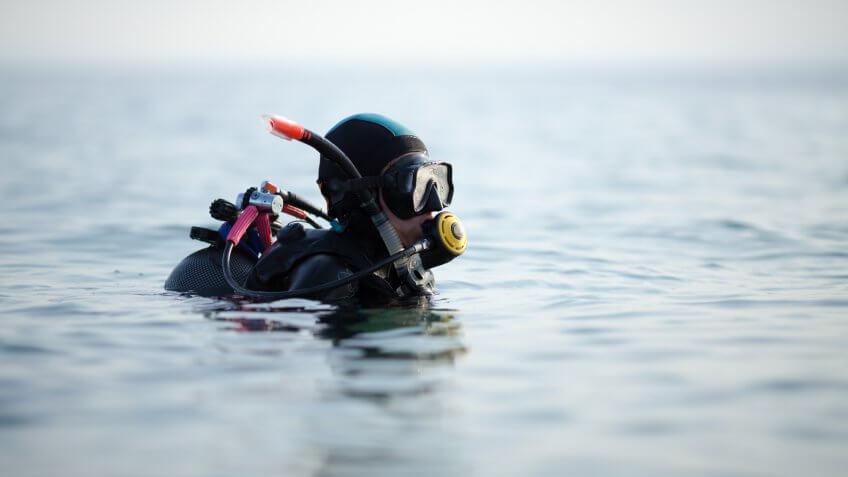 Woman scuba diver going underwater and setting her equipment.