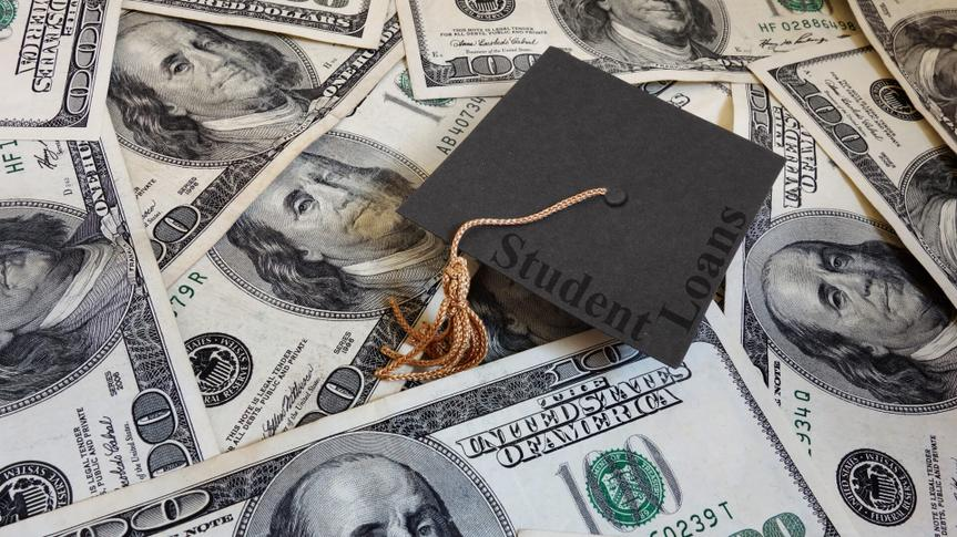 Miniature graduation cap with Student Loans text, on assorted cash.