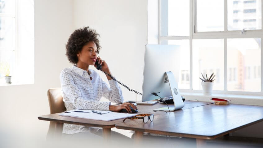 woman talking on phone at her desk in an office