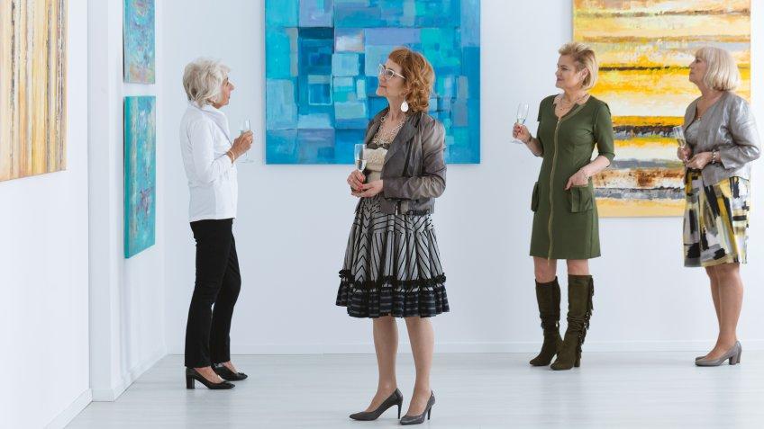 Elegant elder women looking at paintings during opening.