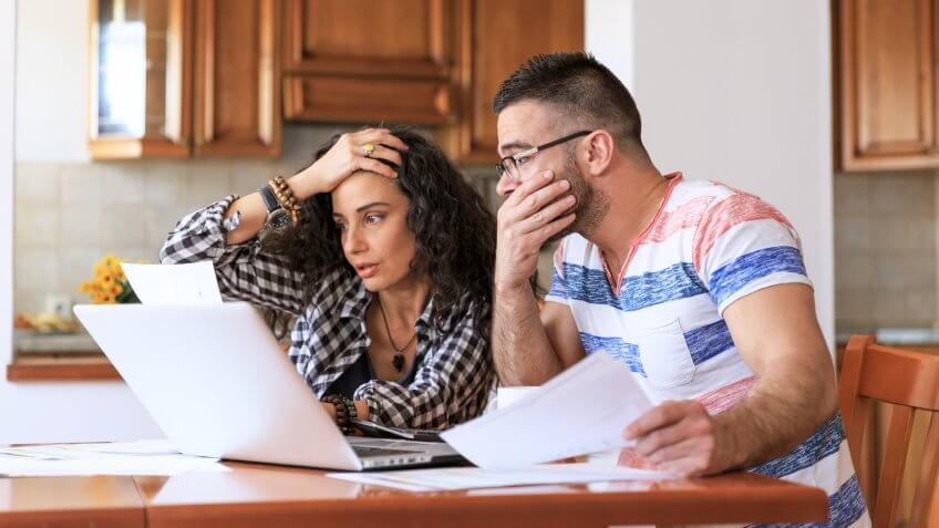Young woman sitting at home and making home finances, with casual clothes.