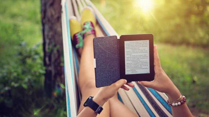 Beautiful girl is reading e-book in the hammock.