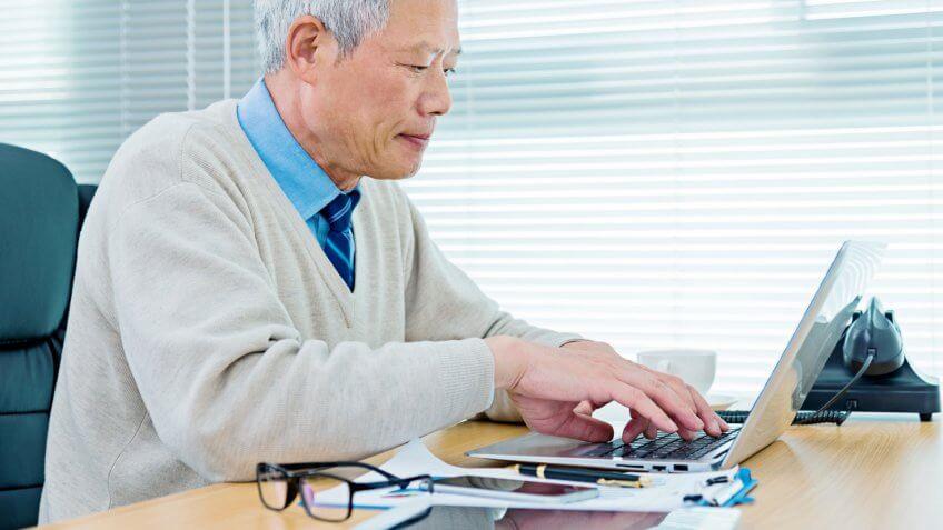 Senior businessman working in office.