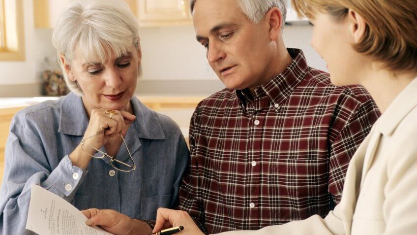 Mature couple talking to financial planner at home.