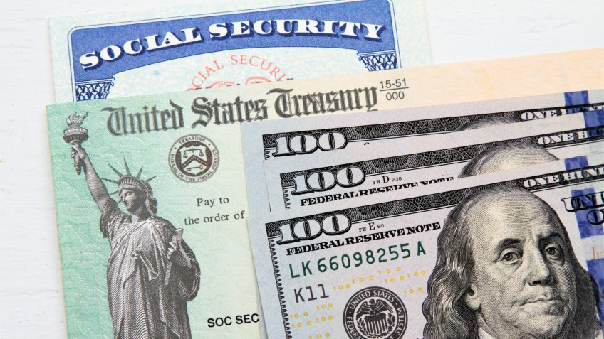 Partial view of Social Security card, US Treasury checks and hundred dollar bills.