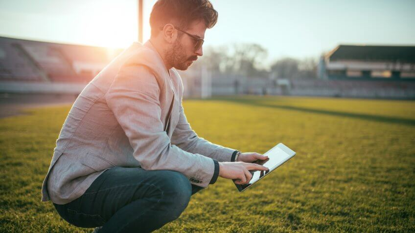 Young and successful footbal manager holding a digital tablet out on the football field.