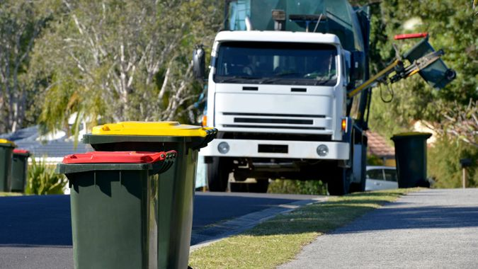 Focus on two Rubbish bins with rubbish truck in background lifting a bin.