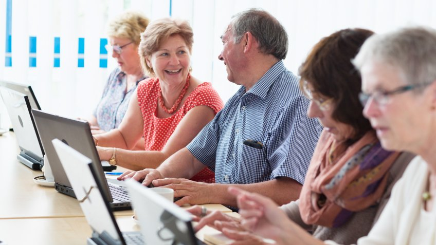 senior adults learning in computer lab.