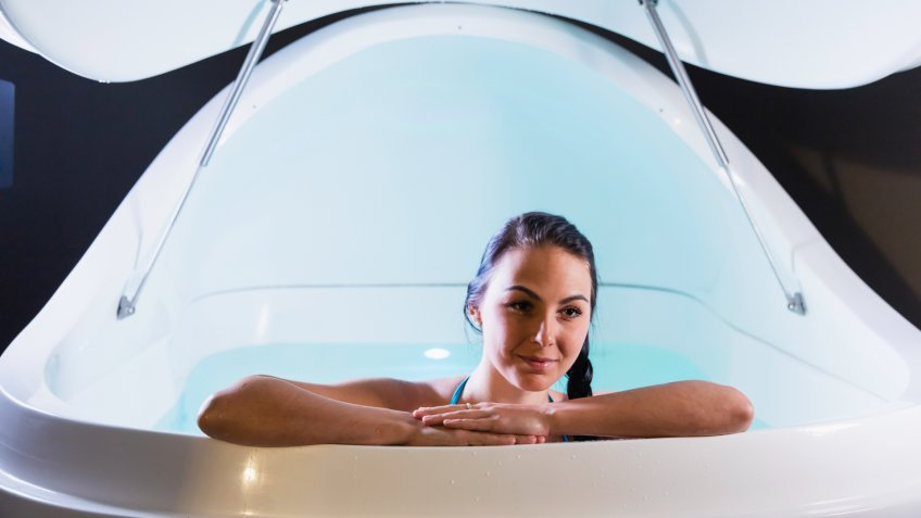 A relaxed young woman leaning on the edge of a sensory deprivation tank.