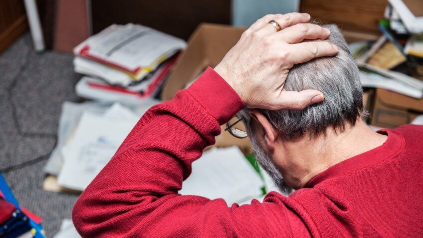 A senior adult man with attention deficit disorder (ADD) is completely frustrated and holding his head as he looks down at chaotic piles of notebooks and documents and paperwork scattered on the floor in his messy office space.