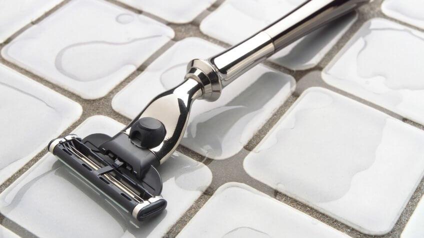 Elegant, modern razor on bathroom wet tile surface.