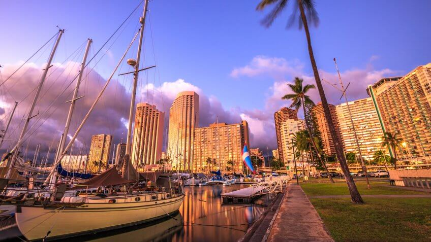 Beautiful panorama of sailing boats docked at the Ala Wai Harbor the largest yacht harbor of Hawaii and Honolulu skyline at twilight.
