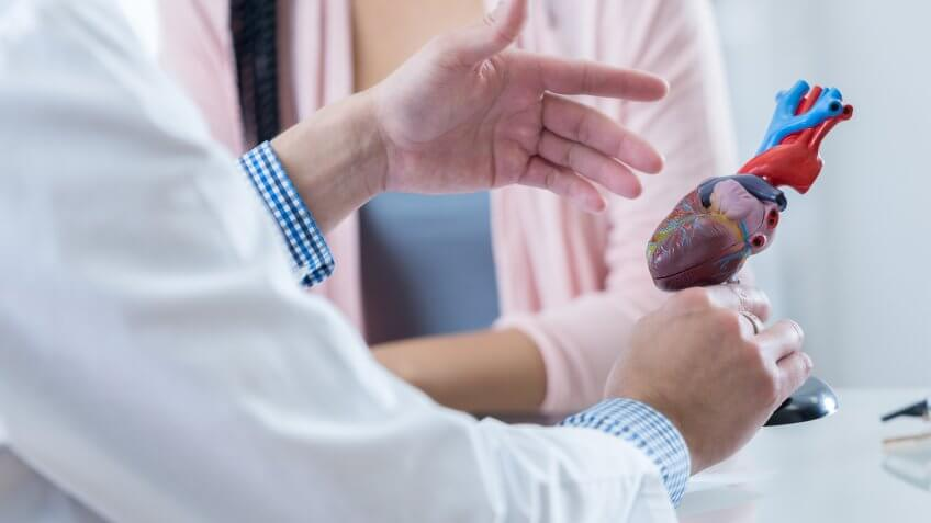 Male cardiologist gestures while discussing diagnosis with an unrecognizable female patient.