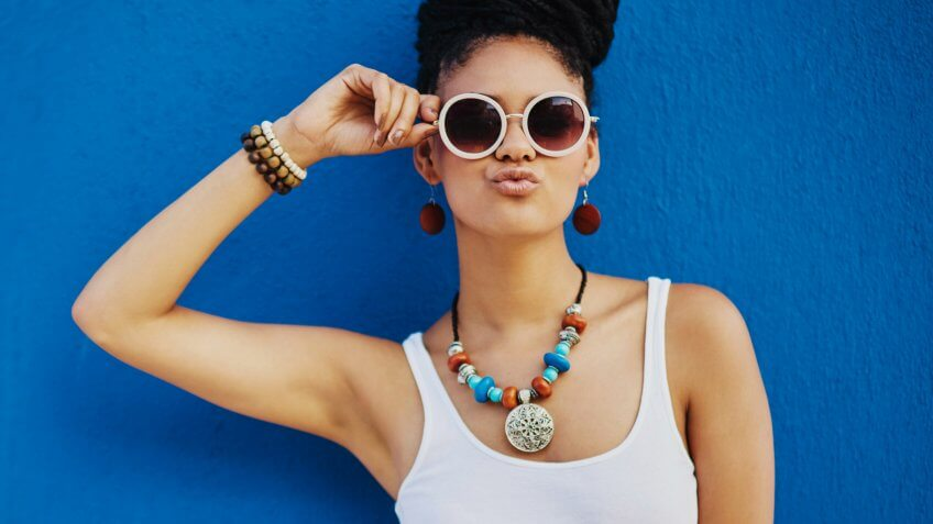 Shot of an attractive young woman wearing funky sunglasses against a blue backgroundhttp://195.