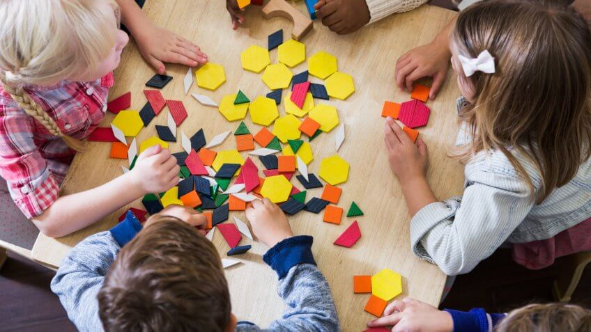 An overhead view of a group of five preschoolers sitting at a table playing with colorful blocks and geometric shapes.