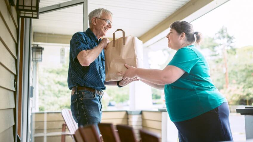 A kind and caring neighbor or friend delivers fresh produce from the grocery store to an elderly man at his home.