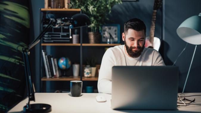 man working on laptop on his finances and emergency fund