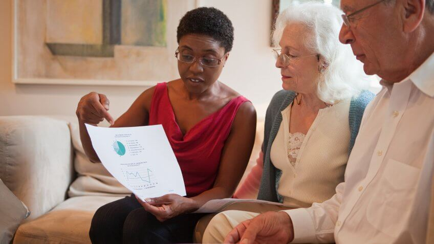 Mid adult woman showing financial paperwork to senior couple.