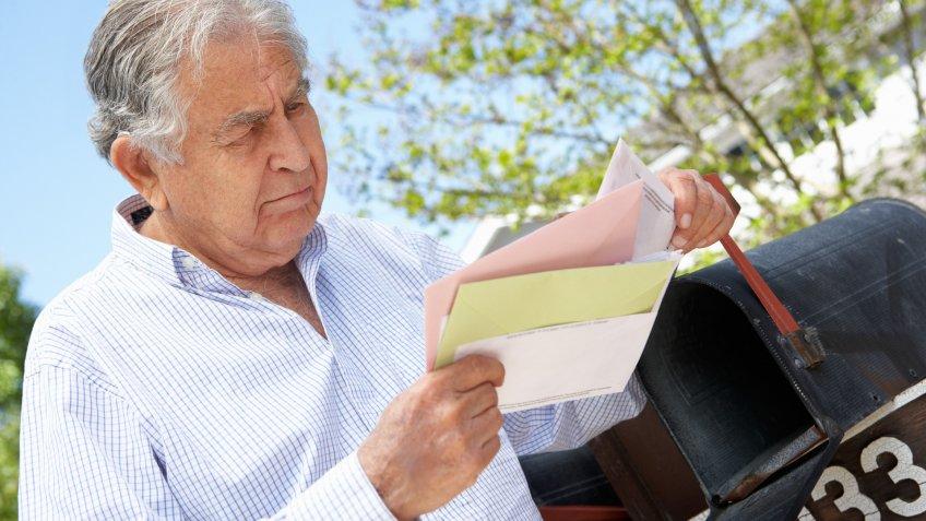 senior-man-checking-mail-bills