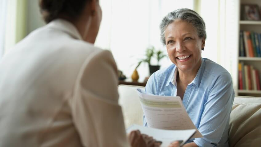 Hispanic saleswoman talking to client in living room.