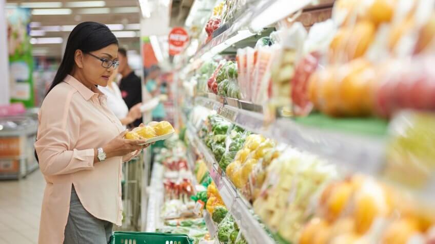 Mature Vietnamese woman choosing vegetables in supermarket.