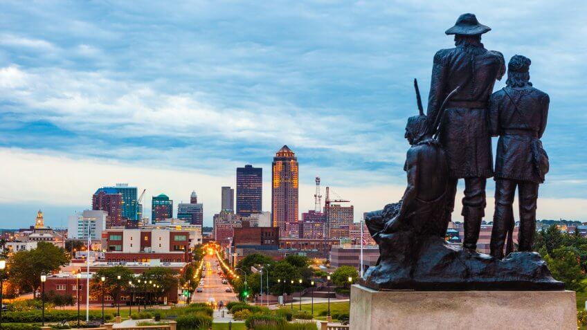 Downtown Des Moines, Iowa with the Pioneers of the Territory statue in the foreground.
