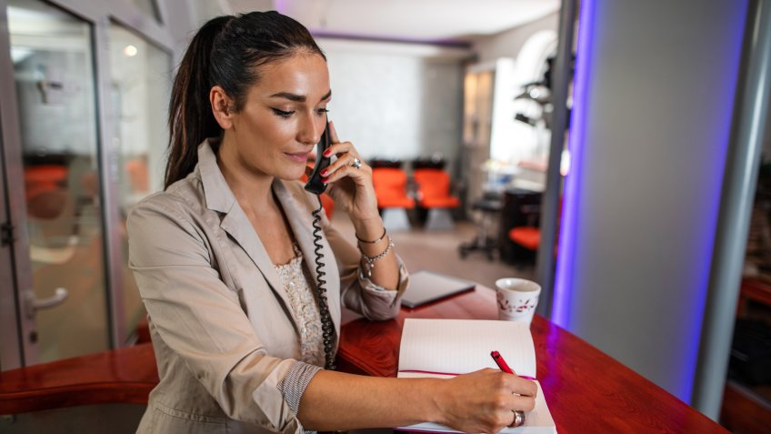 Young woman working in beauty salon and talking on the phone while writing appointment in notebook.