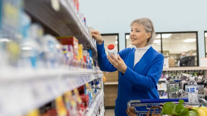 A senior woman stands in the aisle of a pharmacy and reads the pricing of an over the counter medication on the shelf label.