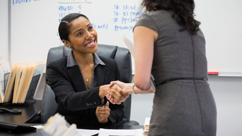 Businesswomen shaking hands in office.