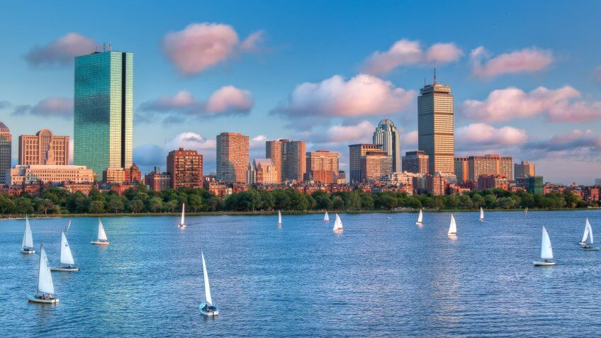 A panoramic view of the full Boston skyline with the Charles River full of sailboats as sunset approaches.