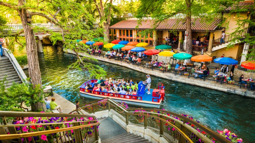 San Antonio, Texas, USA - April 14, 2013: Tourists riding in tour boat and eating at restaurants along The Riverwalk in San Antonio Texas.