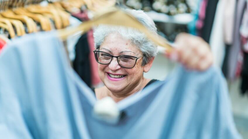 The silver-haired 65-years-old active senior woman shopping in the clothing retail store.
