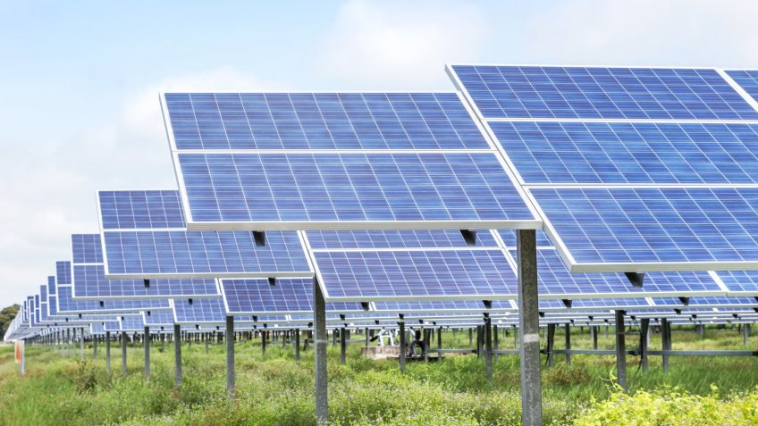 rows array of polycrystalline silicon solar cells or photovoltaics in solar power plant turn up skyward absorb the sunlight from the sun on blue sky background.