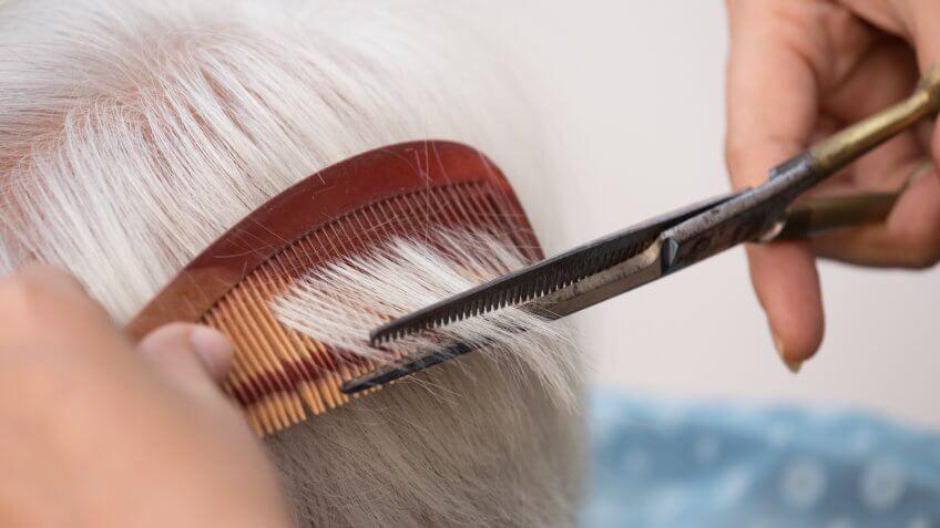 Hair stylist cutting senior woman's gray hair.