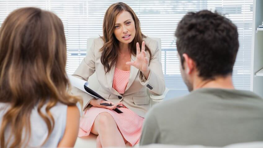 Psychologist discussing with a couple in trouble.