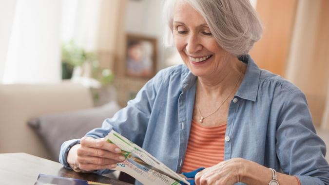 Senior Caucasian woman clipping coupons.