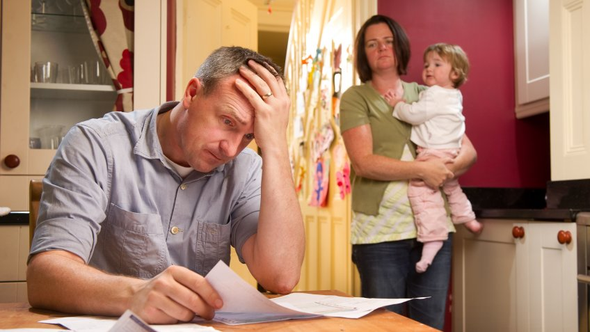 Man stresses over his bill while his wife and child stand in the background.