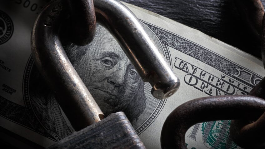An open lock on a stack of $100 bills.